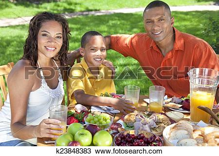 Stock Photo of African American Family Eating Healthy Food Outside.