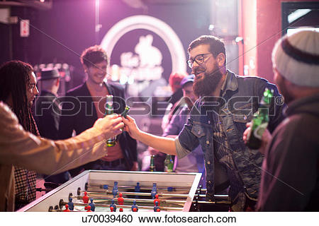 Stock Photography of Group of friends and table football game in.