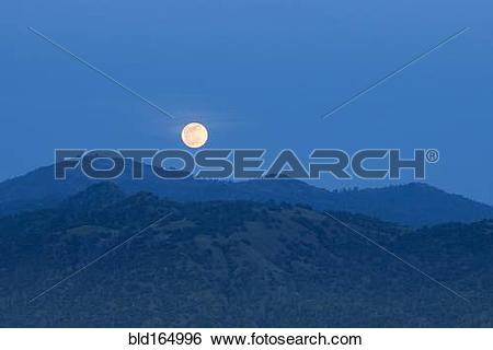 Stock Images of Glowing moon rising over foothills, Oakhurst.