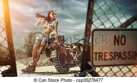Picture of Sexy biker woman with the gun entering forbidden area.
