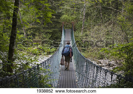 Stock Photo of A Person Walking Over A Suspension Bridge In China.