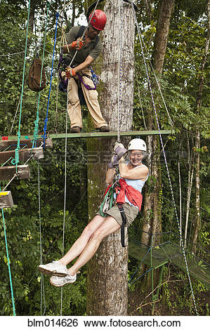 Stock Images of Woman being helped onto zip line in forest.