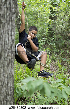 Stock Photo of Hispanic boy swings on rope in forest x25489802.