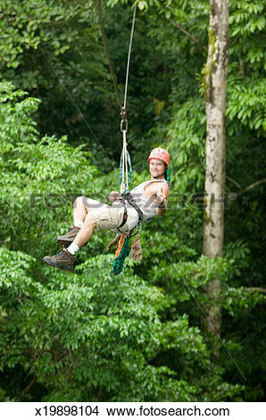 Stock Photo of Man hanging on abseiling rope in forest x19898104.