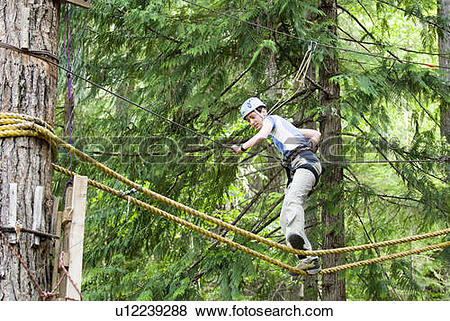 Pictures of A woman works her way through a high ropes course at.