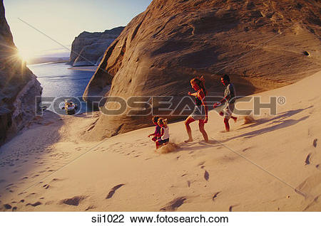 Stock Photo of Young family running down the sand dunes on the.