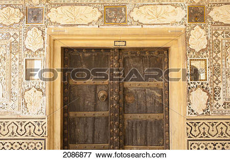 Picture of Wooden door with rivets and walls with ornate tile at.
