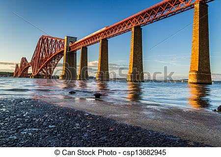 Stock Photo of Train riding on the Forth Road Bridge at sunset.