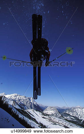 Stock Photograph of Young man catches big air while skiing at.