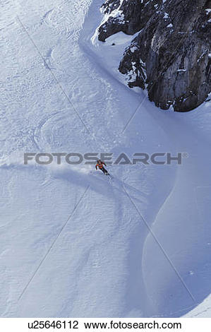 Stock Photo of Young man skiing on ungroomed slope near Fortress.