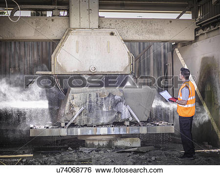 Stock Images of Quarry worker inspecting stone saw u74068776.