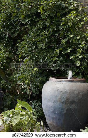 Stock Photograph of PATIO DETAIL: Pottery water fountain, city.