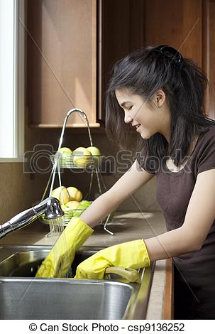 Stock Photo of Teen girl washing dishes at kitchen sink csp9136252.