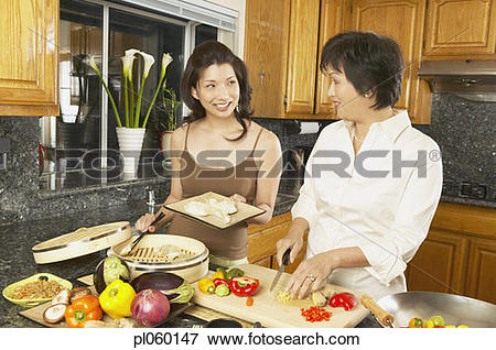 Picture of Asian mother and grown daughter preparing dinner.