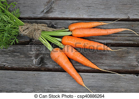 Stock Image of fresh crop of carrots tie beam on wooden table.