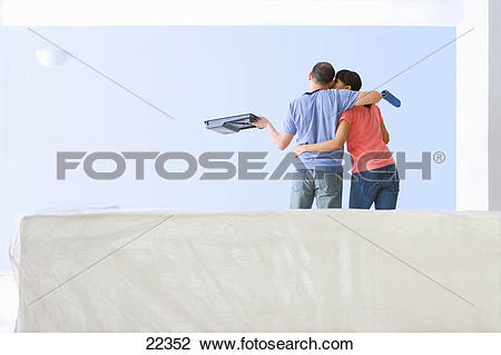 Stock Photo of Couple with paint roller and tray kissing and.