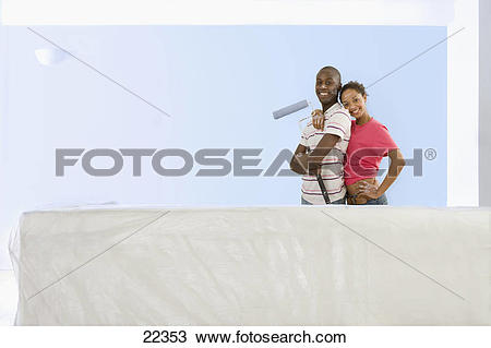 Stock Photo of Smiling couple with paint roller standing next to.