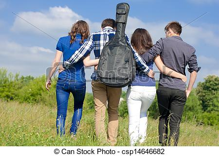 Pictures of Four happy teenage friends walking together outdoors.