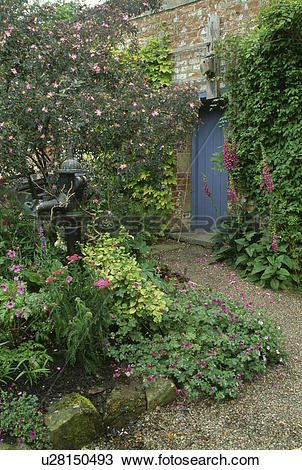 Stock Photo of Old garden pump and small water feature in walled.