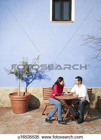 Stock Image of Couple sitting on garden terrace drinking wine.
