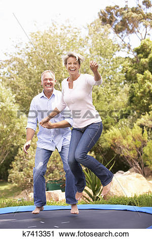 Stock Photography of Couple Jumping On Trampoline In Garden.