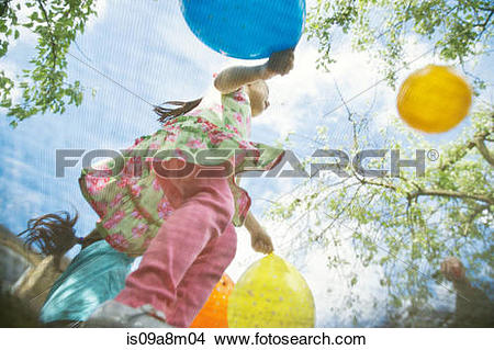 Stock Photo of Young girls bouncing on garden trampoline with.