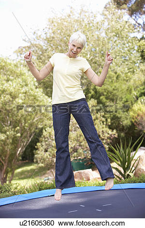 Stock Photography of Senior Woman Jumping On Trampoline In Garden.