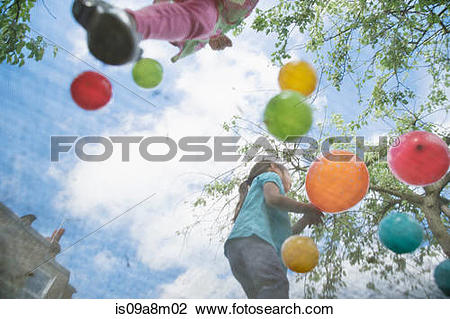 Stock Photo of Young girls jumping on garden trampoline is09a8m02.