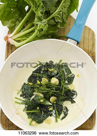 Pictures of Creamed Spinach with Garlic Cloves in a Skillet; From.