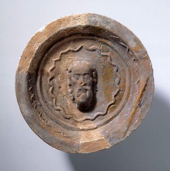 Tellerkachel Medaillonkachel mit Kopf eines Mannes in Wellenkranz.
