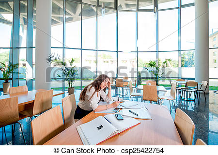 Stock Images of Girl studying in the University canteen. general.