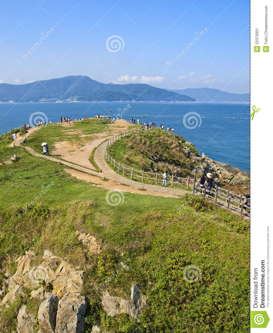 Green Hill By Sea With People Walking Along Paths Stock Photo.