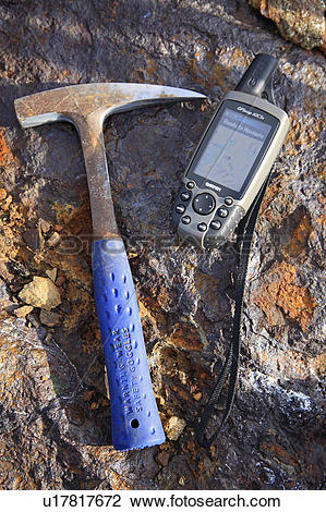 Stock Photo of Mining exploration; rock hammer and GPS unit on.