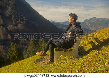 """Stock Photo of """"Woman sitting on a bench, relaxed, sunbathing."""
