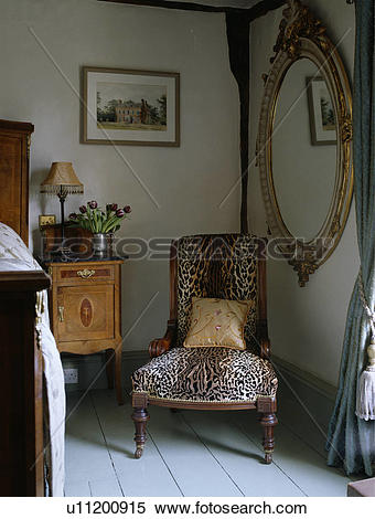 Stock Image of Large ornate gilt mirror on wall above faux.