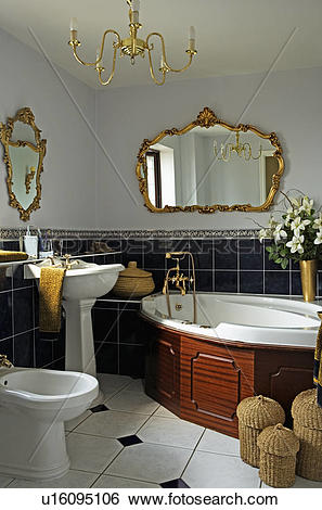 Stock Images of Ornate gilt mirror above corner bath in bathroom.