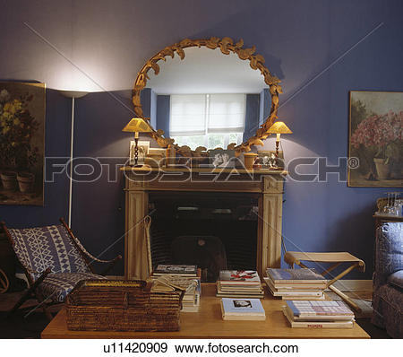 Stock Photograph of Ornate gilt oval mirror and lighted lamps on.