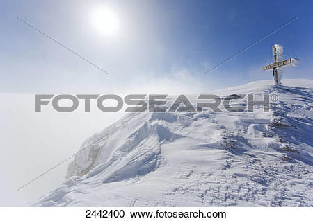 Stock Photography of Summit cross covered with snow on mountain.