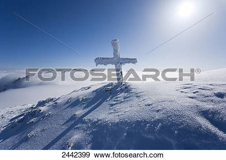 Stock Photograph of Summit cross covered with snow on mountain.