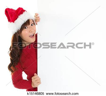 Stock Image of Santa girl peeking from behind blank sign billboard.