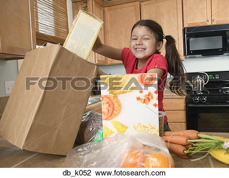 Stock Photo of Hispanic girl unpacking groceries in kitchen.
