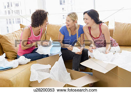 Stock Photo of Three girl friends unpacking boxes in new home.