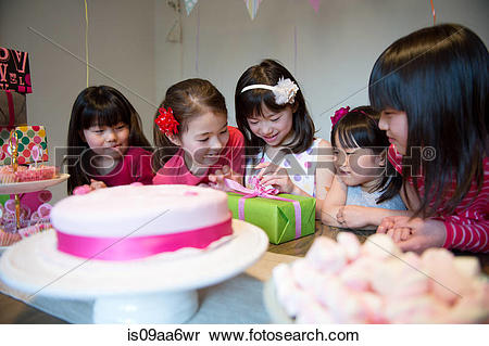 Stock Image of Girl unwrapping birthday present at party is09aa6wr.