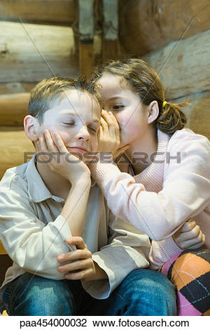 Stock Photo of Girl whispering in boy's ear, boy closing eyes.