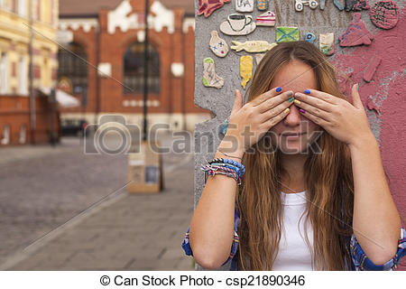 Stock Photo of Pretty young girl closing eyes with hands on the.
