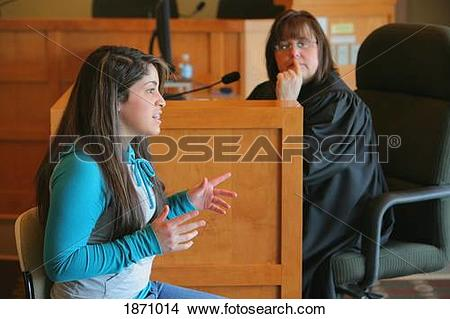 Stock Photo of a teenage girl giving her testimony before a judge.