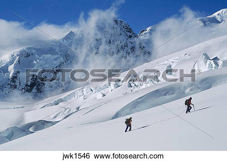 Stock Images of Two mountaineers ascend the Tasman Glacier below.
