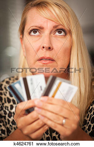 Stock Photography of Upset Woman Glaring At Her Many Credit Cards.