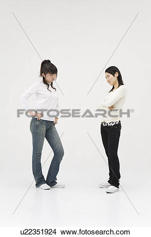Stock Photo of Two young women glaring at each other u22351924.