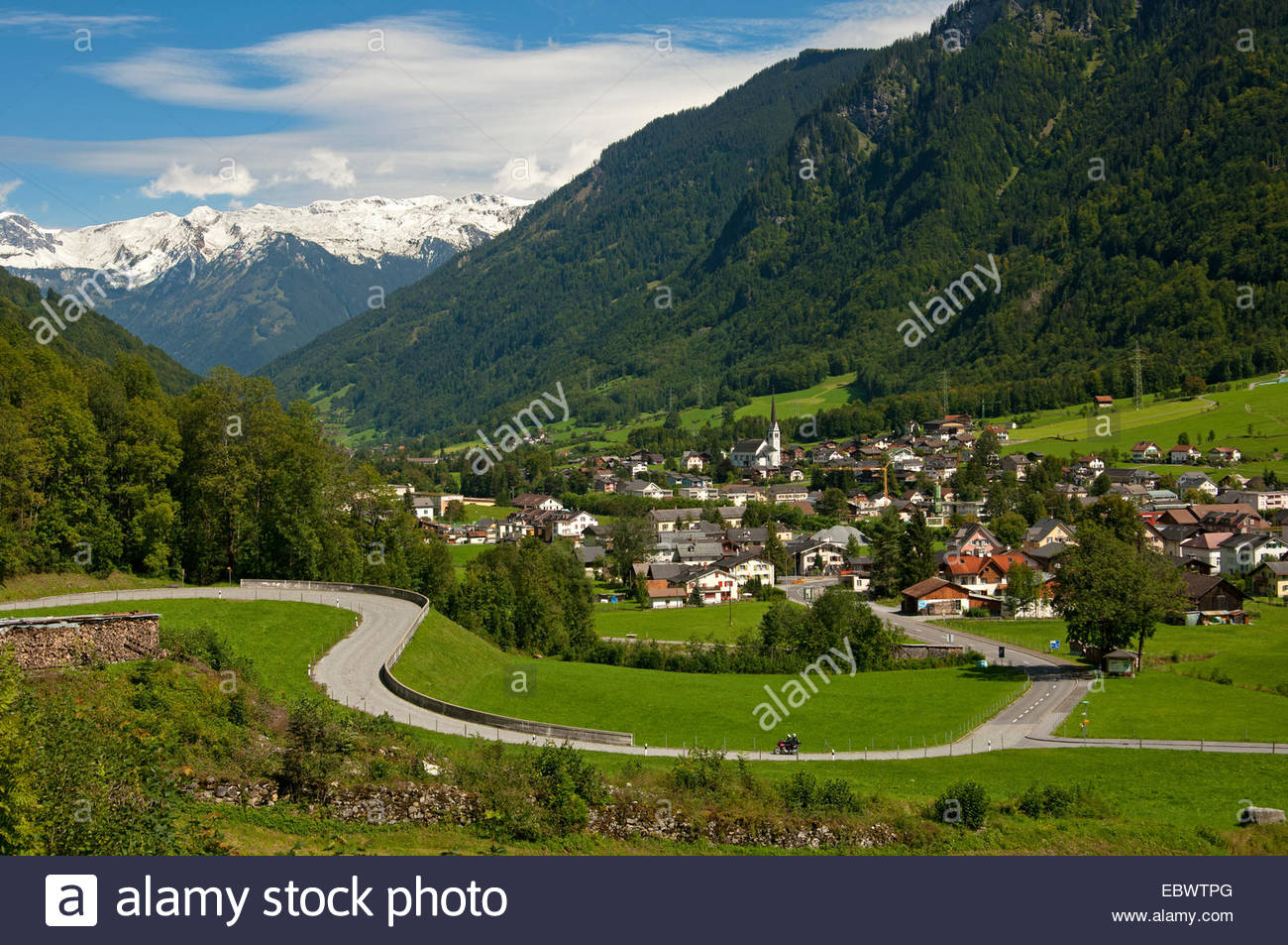 Winding road in front of the village of Linthal, Glarus Alps at.